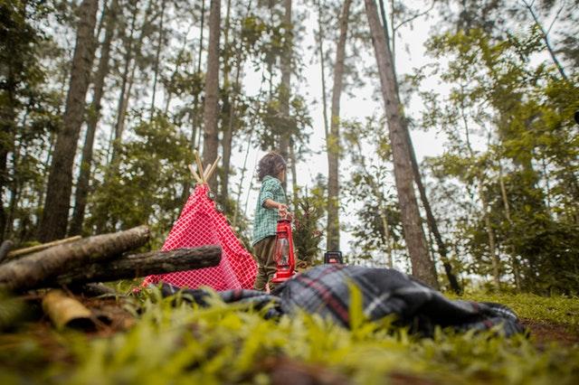 dítě s růžovým stanem v lesích.jpg