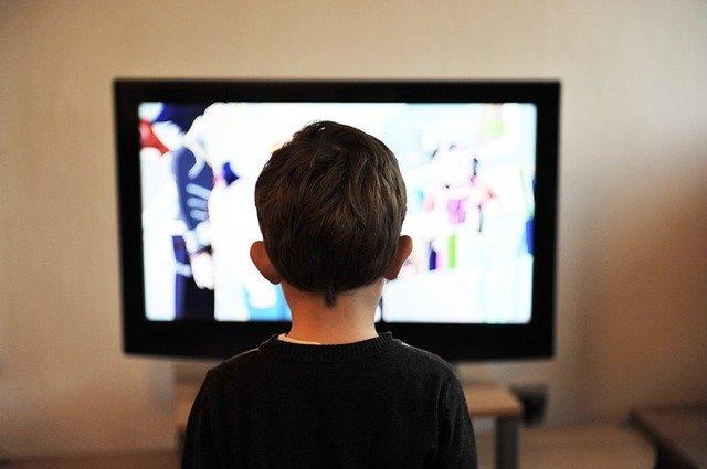 kluk pře televizí v černém tričku, stojí zády
